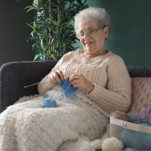 Old woman knitting in warm