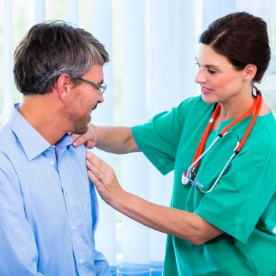 Doctor assessing male patient shoulder